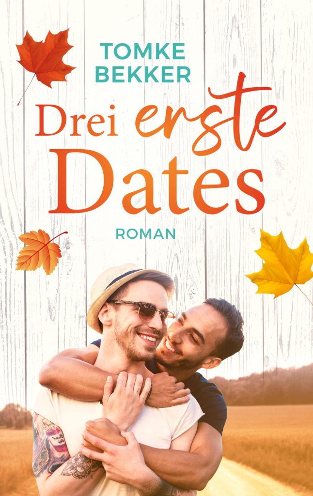 """Cover von """"Drei erste Dates"""": Zwei Männer vor einer herbstlichen Kulisse mit Feldern, der hintere legt den Arm um den vorderen, beide wirken glücklich und lächeln"""